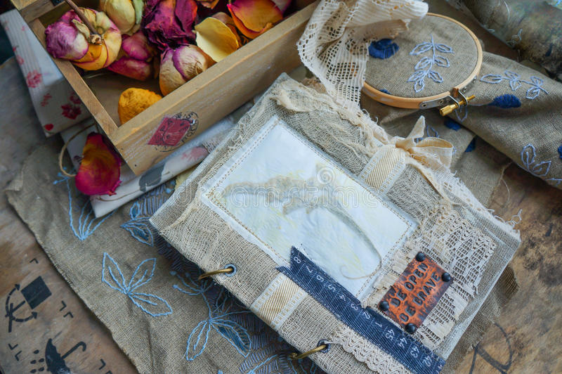 Still life with a vintage notebook, dry flowers and an embroider. Still life with a vintage handmade scrapbooking, dry flowers and an embroider royalty free stock photo