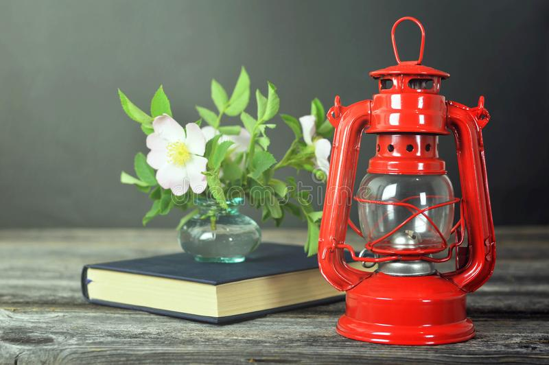 Still life with vintage oil lamp, book and dog rose flowers in vase on wooden background royalty free stock photo