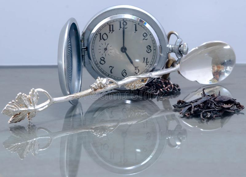 Still life of a vintage watch with an opening lid, tea leaves and a silver spoon stock photos
