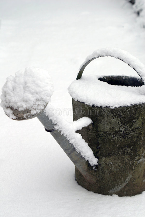 Still-life of a watering-can and snow royalty free stock image