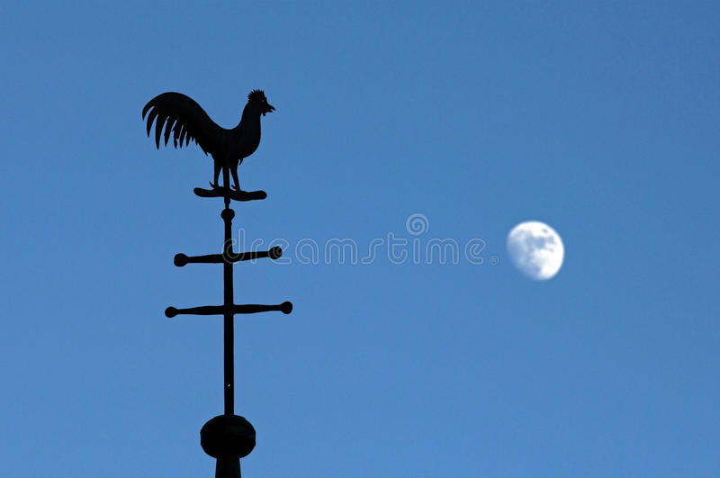 Still life of weathercock and moon in blue sky stock image
