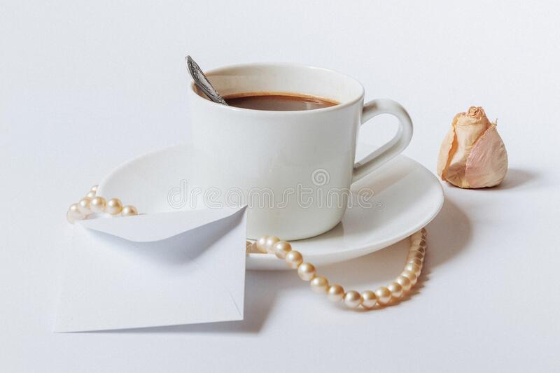 A still life with a white ceramic cup of coffee, a small white envelope, and the dried rose`s bud.  royalty free stock photo
