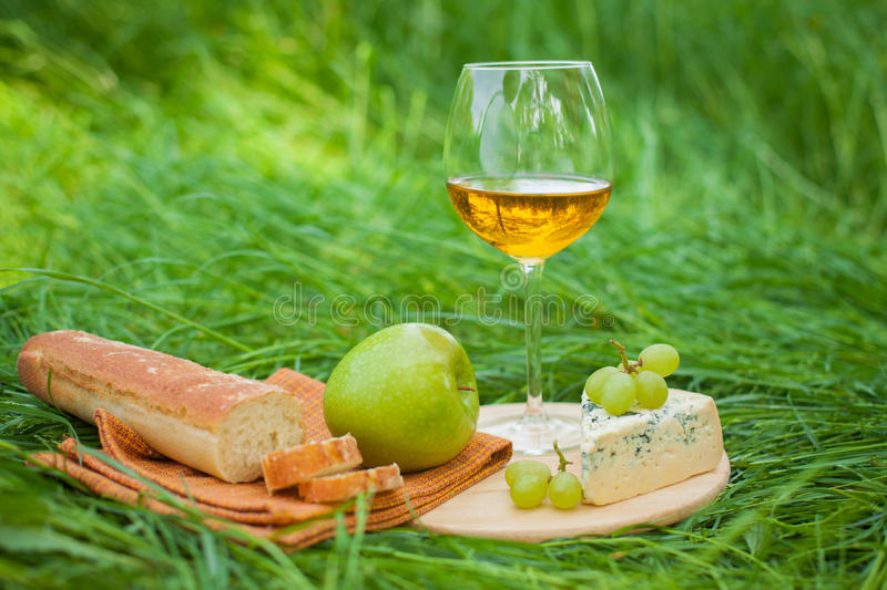 Still life with white wine, baguette, cheese, grape and apple stock image