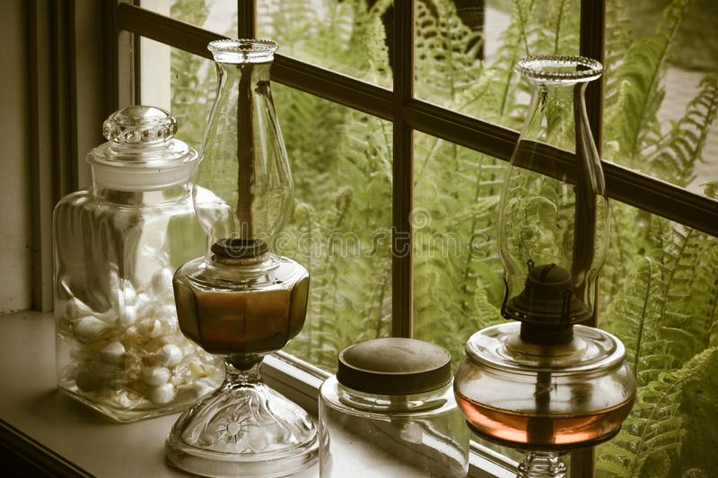 Still life on a windowsill. Antique or vintage hurricane lanterns, jars, and glass container on a windowsill. Bright and tall green ferns are outside the window royalty free stock image