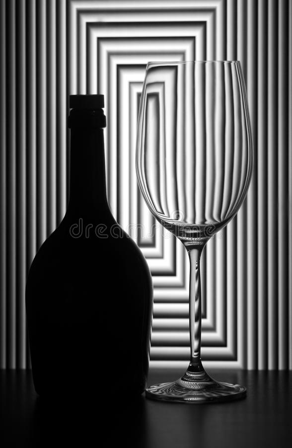 Still life with wine glass and bottle. On graphic abstract background stock photography