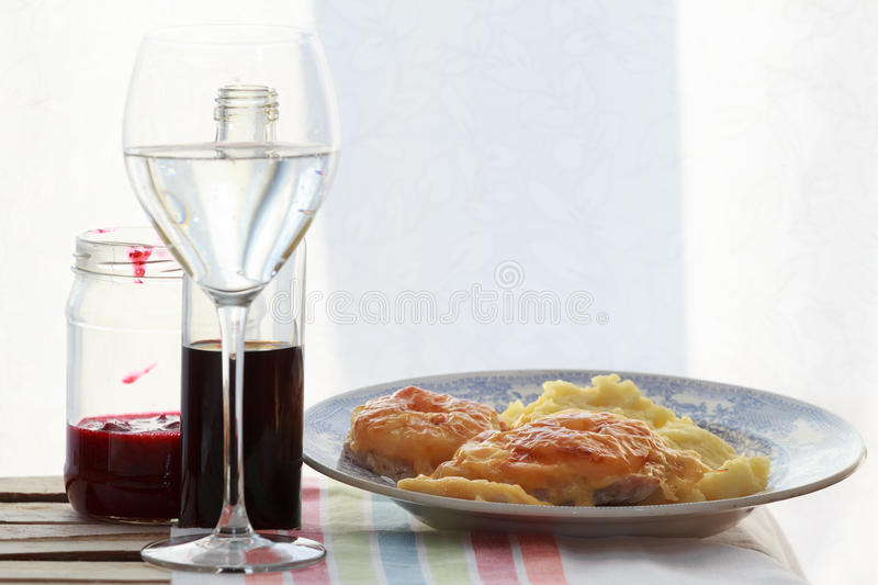 Still life of wine glass, soy sauce bottle, fruit sauce jar and roasted meat slices with mashed potato royalty free stock photography