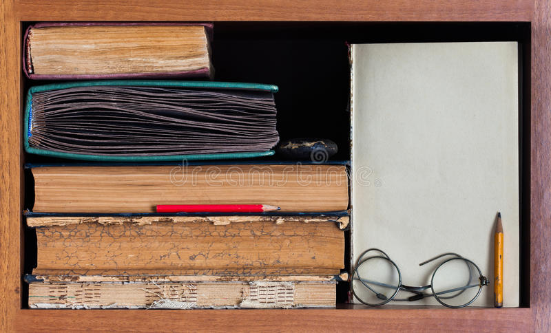 Still life with wooden book shelf, rare antique books, textured pages, pencils, blank paper scroll and retro design royalty free stock image