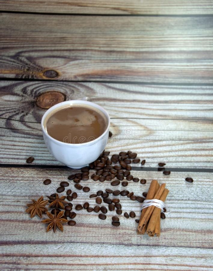 Still life on a wooden table, a cup of cappuccino, cinnamon, star anise and coffee beans. Close-up royalty free stock photo