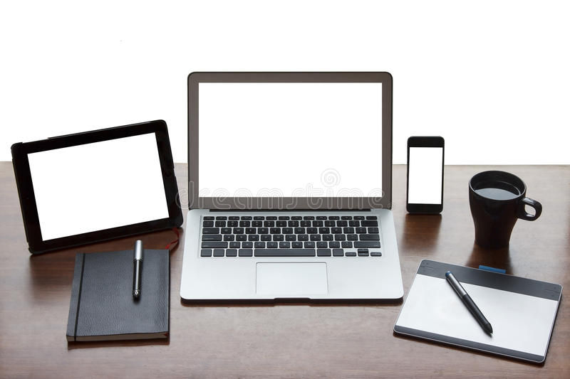 Still life of working desk with electronics. Still-life of work desk with laptop, phone, tablet, notebook, graphic tablet and coffee cup. White screens on all stock image