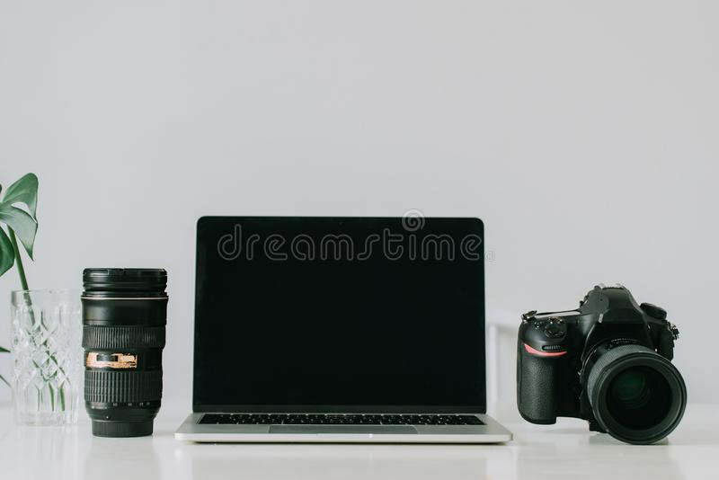 Still life working from home desk with professional photographic equipment, camera, lens, computer monitor, electronics indoors.  royalty free stock photos