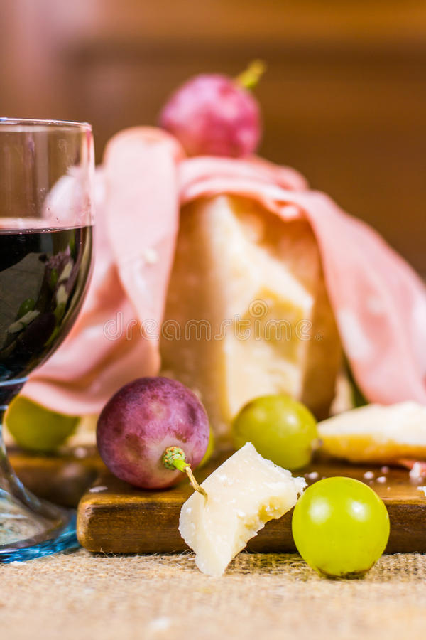 Still life - yellow and red muscat grape, cheese, salami and a glass of red wine on a wooden board and canvas stock images