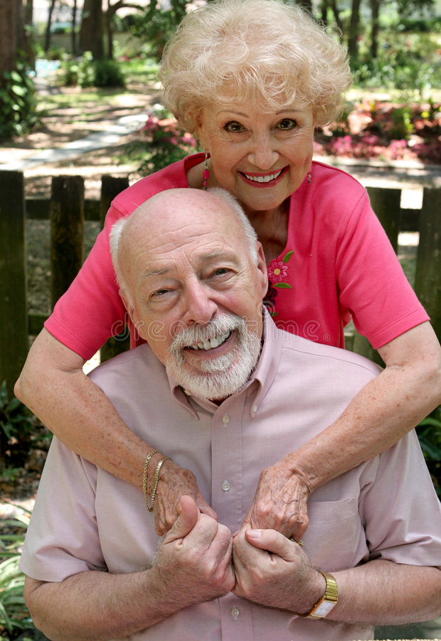 Still In Love. A happy senior couple embracing outdoors. They are still in love after many years together stock photography