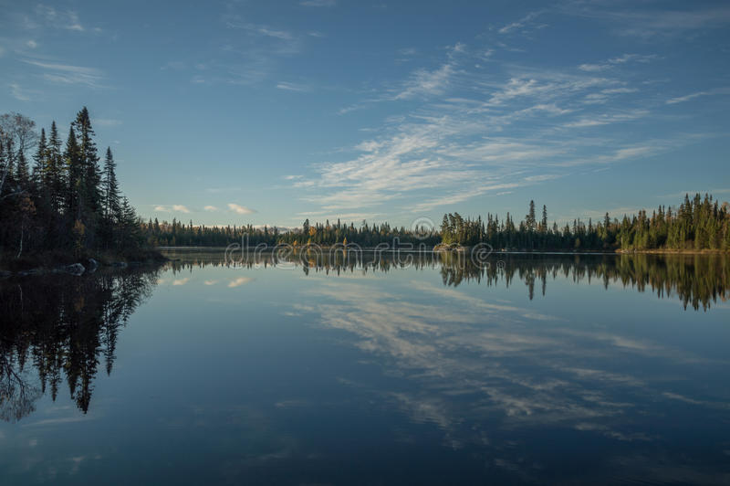 Still Northern Ontario lake in early morning with reflected cloudscape and trees stock image