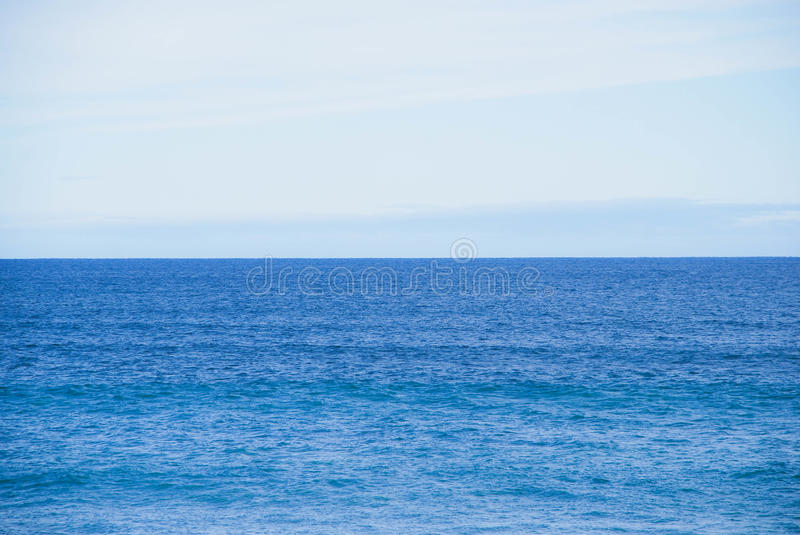 Still ocean horizon, no waves, no objects in view, straight water line. Straight water horizon line, daylight, some altostratus clouds in the sky, simple royalty free stock images