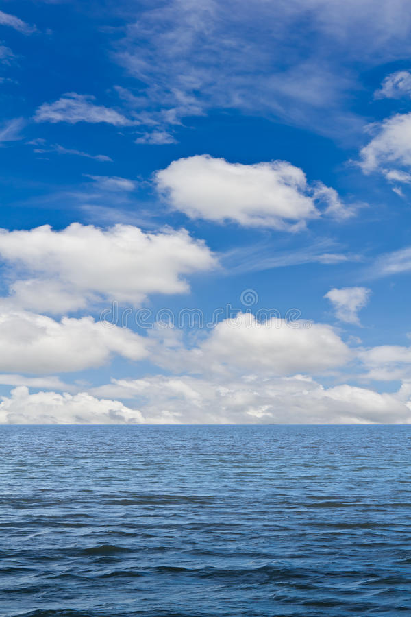 Still sea and blue sky with white cloud stock image