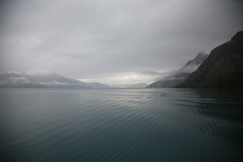 Still and serene grey winter morning on Lake Wakatipu, New Zealand royalty free stock image