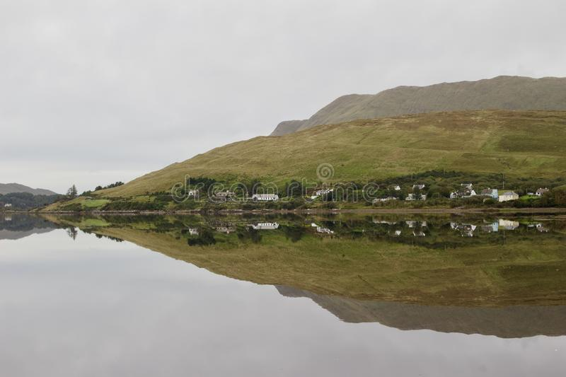 Still water creates a reflection of homes along a lake in rural Connemara in western Ireland. County Galway showing a peaceful hillside with overcast sky royalty free stock photo