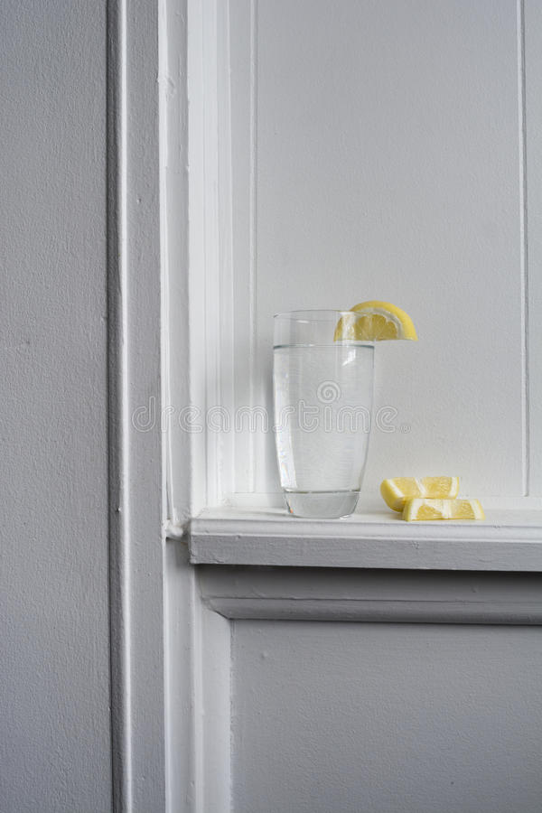 Still Water With Lemon. Glass of still water with lemon sitting on white wood ledge royalty free stock image