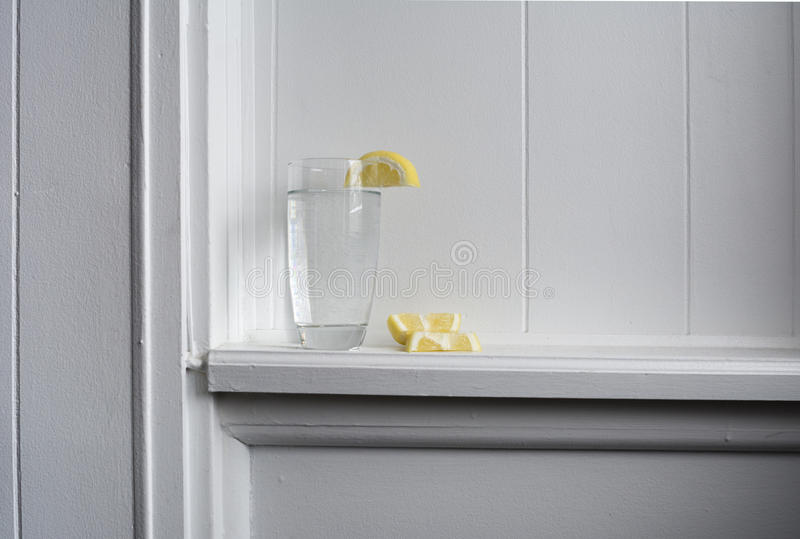 Still Water With Lemon. Glass of still water with lemon sitting on white wood ledge royalty free stock photos