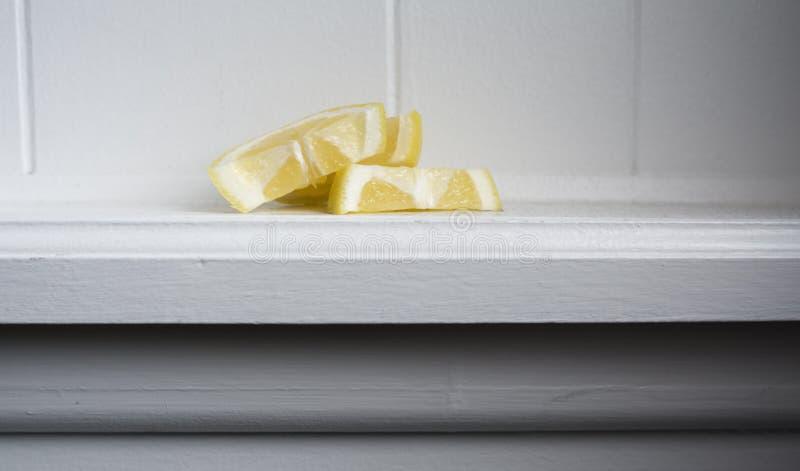 Still Water With Lemon. Lemon slices sitting on white wood ledge stock photo