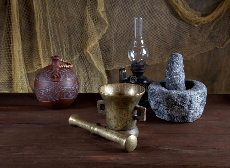 Stillbild-liv med mortlar och en olje- lampa på ett gammalt bordlägger arkivfoton