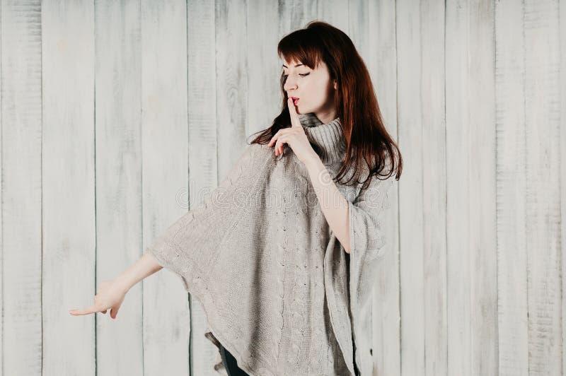 stille Eine junge Frau bitten um Ruhe, ruhig oder Geheimhaltung mit dem Finger auf den Lippen, schauend sideway und zeigen mit de lizenzfreies stockbild