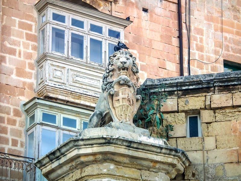 Stille straten van de hoofdstad van Malta - Valletta Het standbeeld van Leeuw die een schild op de hoek van de Straat en de Aarts stock afbeelding