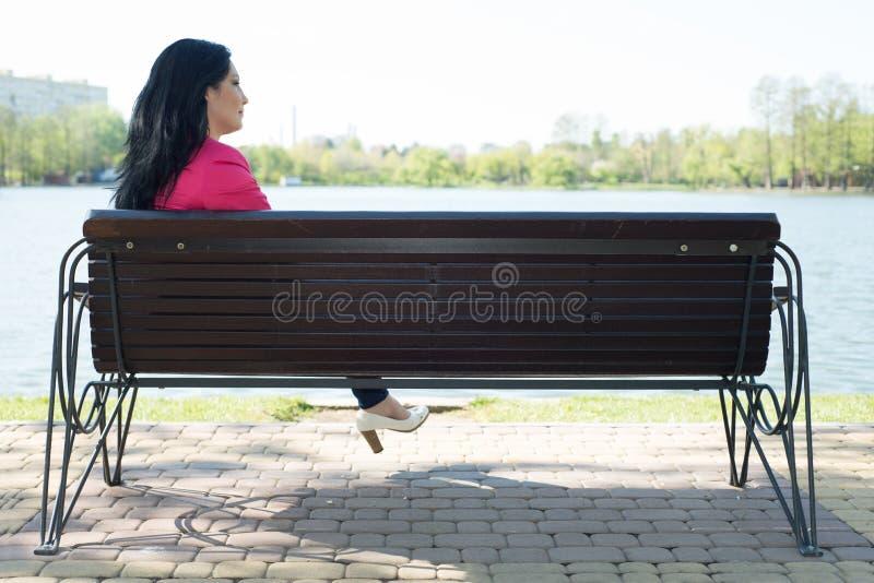 Stille vrouwenzitting op bank stock foto