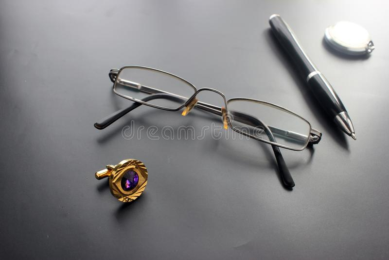 Stilleben, affär, kontorstillförsel eller utbildningsbegrepp: en sikt av en tillbakalutad stoppning, exponeringsglas, en penna, e arkivbilder
