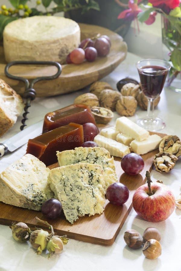 Stilleben av Asturian ädelost cabrales med den söta kvitten, muttrar, hasselnötter, druvor, äpplet och rött vin royaltyfria bilder