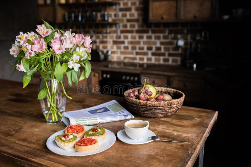 Stilleben av blommor, tidningen, frukosten med kakor, kaffe och frukter fotografering för bildbyråer