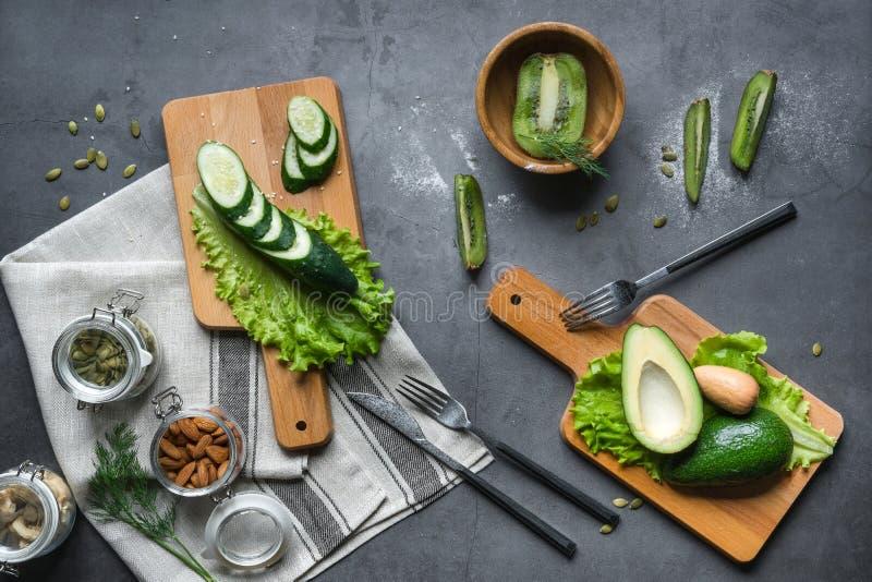 Stilleben av gröna grönsaker och frukter på en grå bakgrund på träbräden Gurkor avokadon, grönsallat, kiwi, muttrar, mandlar royaltyfria bilder