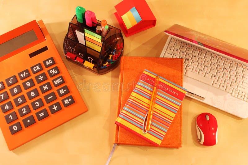 Stilleben av kontorsskrivbordet i orange färg royaltyfri fotografi