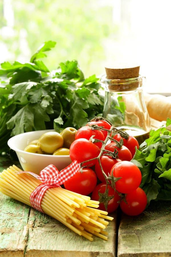 Stilleben av oliv, örter, tomater och italiensk pasta arkivbilder