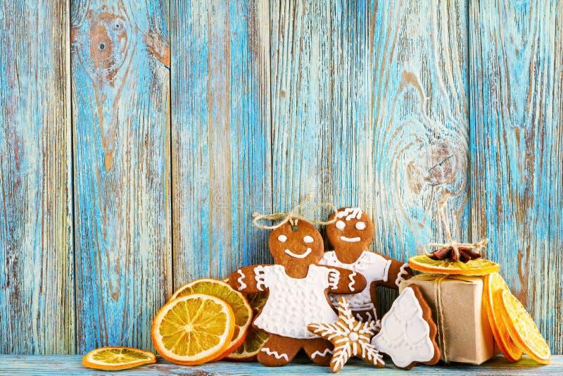 Stilleben av pepparkakan, pepparkakamän, torkade apelsiner på blå träbakgrund, bakgrund för jul eller för nytt år royaltyfria foton