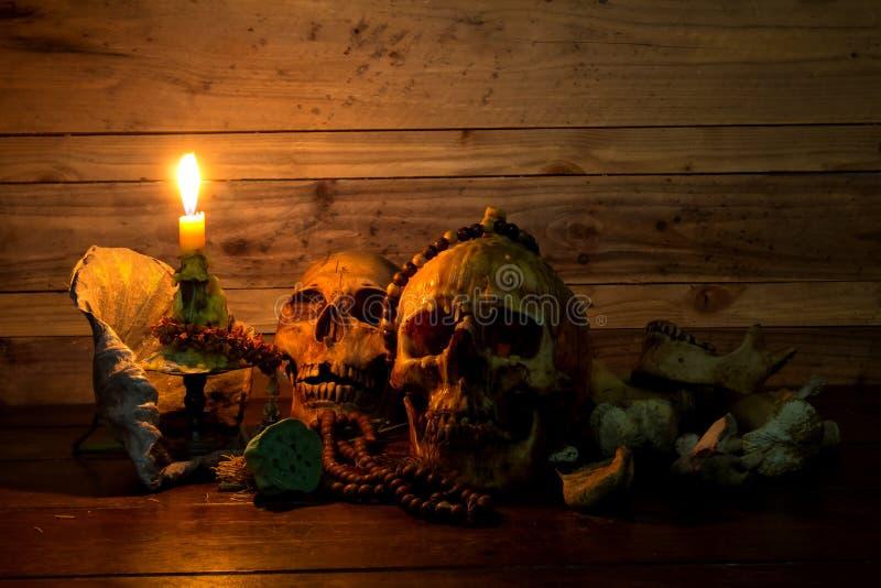 Stilleben av skallen med stearinljusljus på träplanka royaltyfria bilder