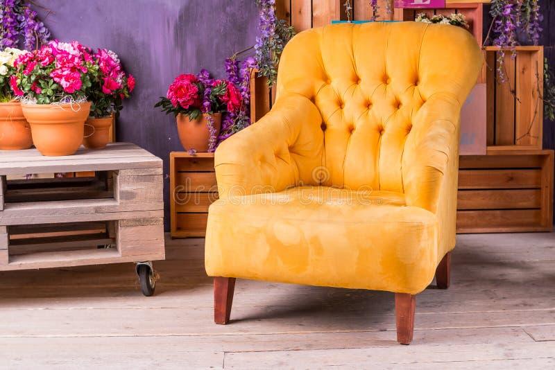 Stilleben av tappningstol i vardagsrum Terrassvardagsrum med bekväm gul armstol, soffor i ett lyxigt hus royaltyfri fotografi