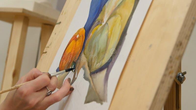 Stilleben för pumpa för målning för hand för kvinna` s med vattenfärger på staffli royaltyfri foto