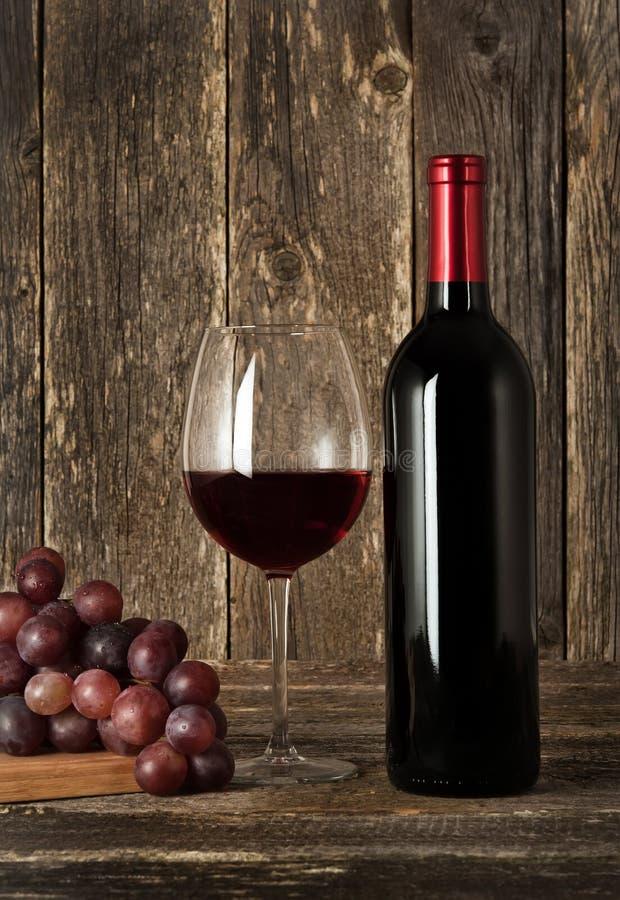 Stilleben. Flaska av rött vin, exponeringsglas och druvor arkivfoto