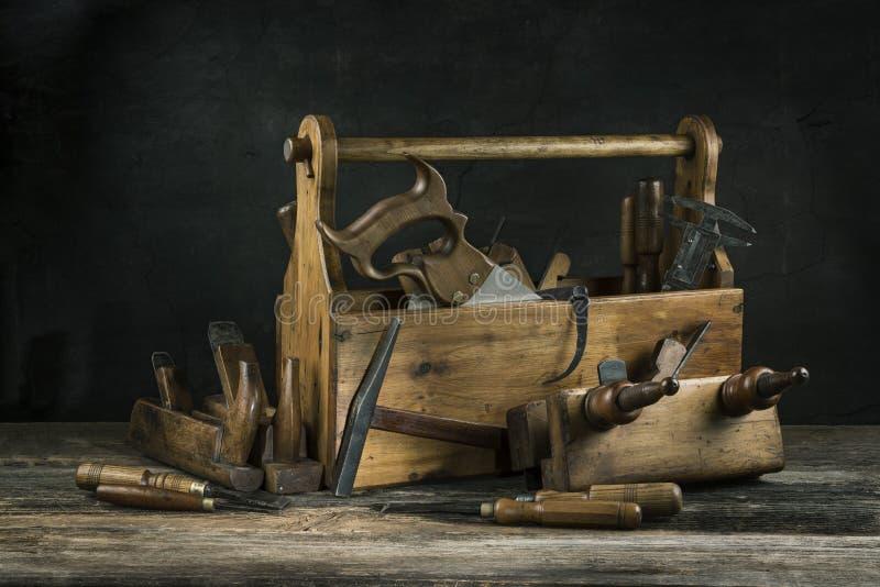 Stilleben - gammal trätappningtoolbox med hammare, sågen, stämjärn, nivån och plattång i snickeri royaltyfri bild