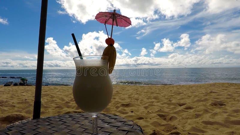 Stilleben: Hav, strand, moln och coctail arkivbilder