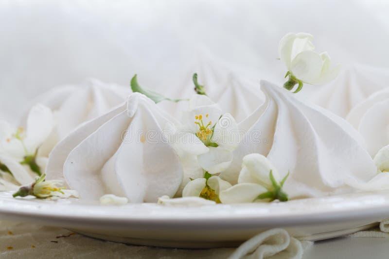 Stilleben i tappningstil med den marängkyssar och körsbäret blommar på den rostade trätabellen royaltyfri fotografi