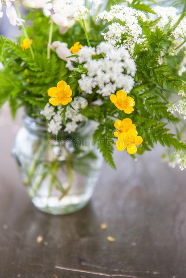 Stilleben med blommor och gräs för bukett lösa på gammal träflik royaltyfria foton