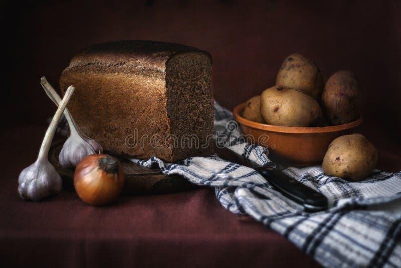 Stilleben med brödpotatisar, lökar och vitlök royaltyfri bild