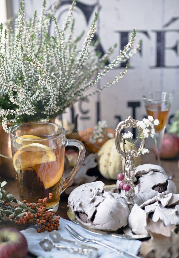 Stilleben med chokladmarängar, te med citronen, äpplet, bergaskaen, pumpa, likör, ljung, tappninggaffeln och sockerkoppar royaltyfria foton