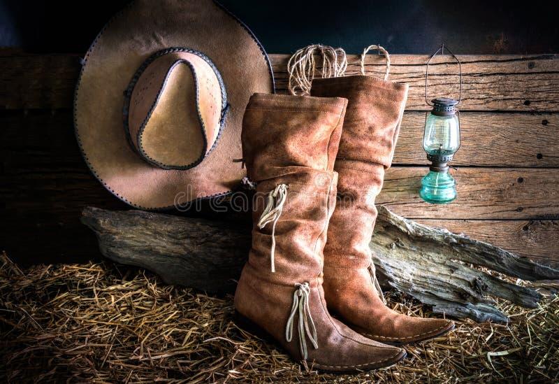 Stilleben med cowboyhatten och traditionella läderkängor royaltyfri foto