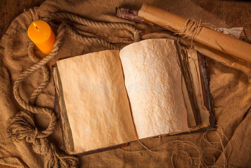 Stilleben med den öppnade antika boken arkivbilder