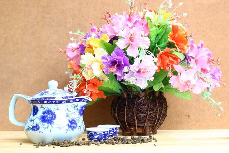 Stilleben med den färgglade gruppen i den wood vasen och te lägger in på trätabellen royaltyfria bilder