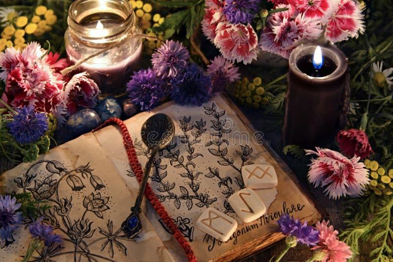 Stilleben med den gamla boken med botaniska teckningar, svartstearinljus, blommor och ritual anmärker royaltyfri foto