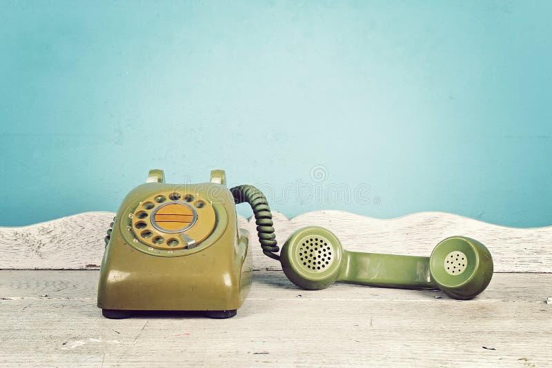 Stilleben med den gamla gröna telefonen på trätabellen, roterande telefon royaltyfria foton